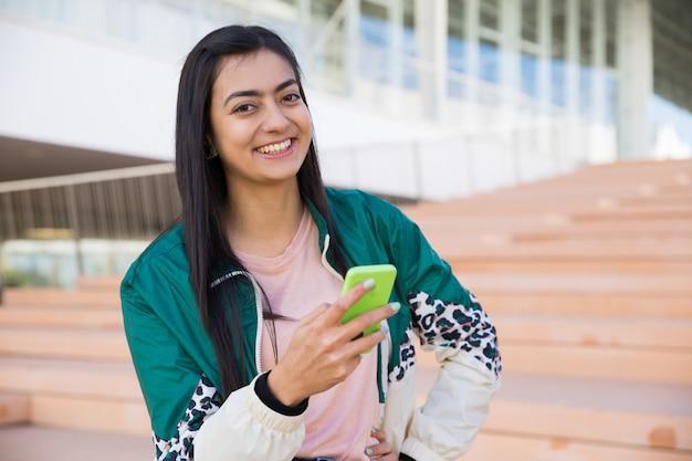 Linda mulher na escada segurando o telefone na mão, sorrindo