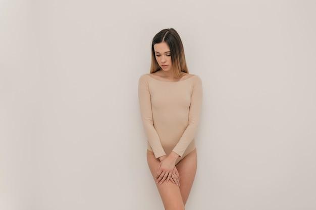 Linda mulher natural em pé sobre uma parede branca, vestida com um corpo bege e curtindo a vida