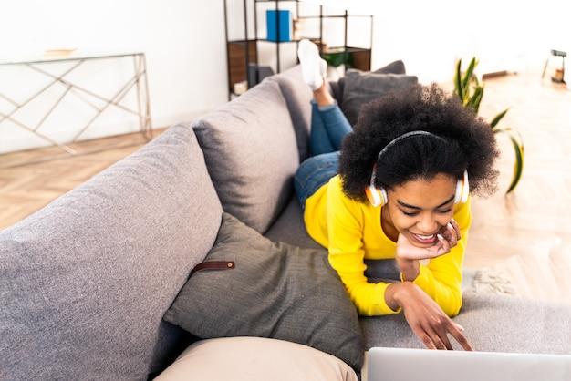 Linda mulher negra adulta em casa ouvindo música online com o computador, laptop e fones de ouvido - linda garota negra trabalhando remotamente online em casa
