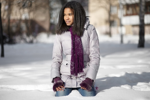 Linda mulher negra americana sorridente, sentado na neve ao ar livre