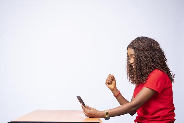 Linda mulher negra, animada, olhando para o telefone