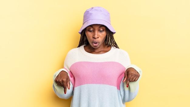 Linda mulher negra com a boca aberta apontando para baixo com as duas mãos, parecendo chocada, espantada e surpresa