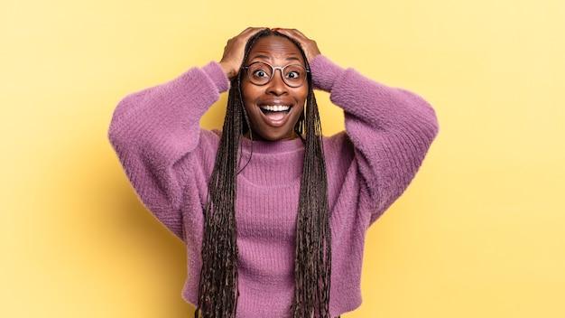 Linda mulher negra com as mãos na cabeça erguendo a boca aberta, sentindo-se extremamente sortuda, surpresa, animada e feliz