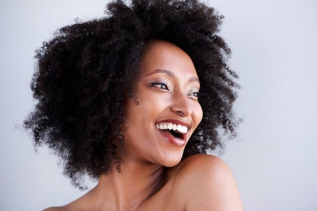 Linda mulher negra com cabelo encaracolado, rindo e olhando para longe