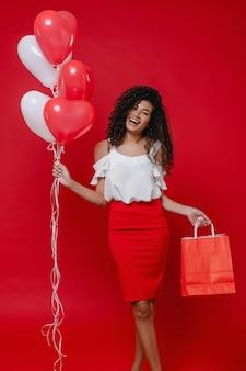 Linda mulher negra com coração colorido em forma de balões e sacolas na parede vermelha