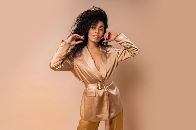 Linda mulher negra com lindos cabelos ondulados num elegante terno de cetim dourado posando sobre uma parede bege. look da moda primavera.