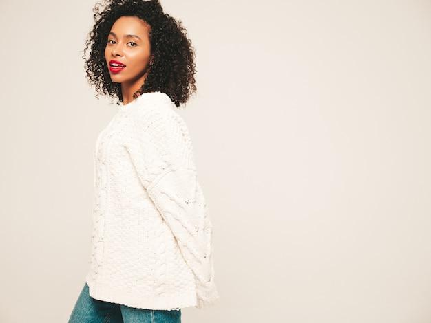 Linda mulher negra com penteado afro cachos e lábios vermelhos. modelo sorridente em roupas da moda jeans e suéter de inverno.