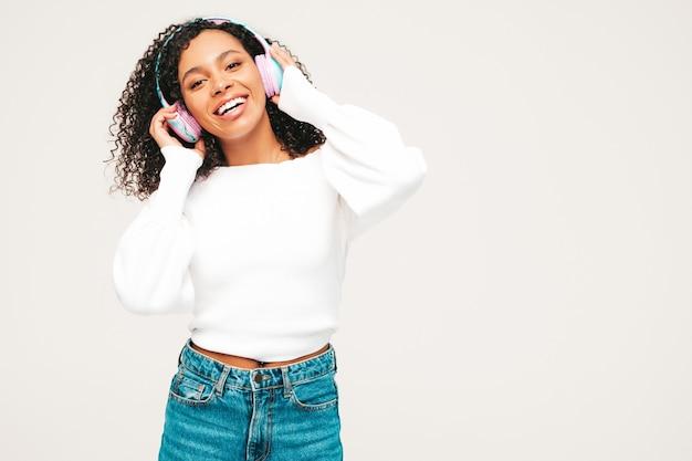 Linda mulher negra com penteado de cachos afro. modelo sorridente de suéter e jeans