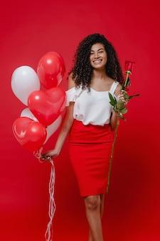 Linda mulher negra com rosa e coração em forma de balões isolados no vermelho