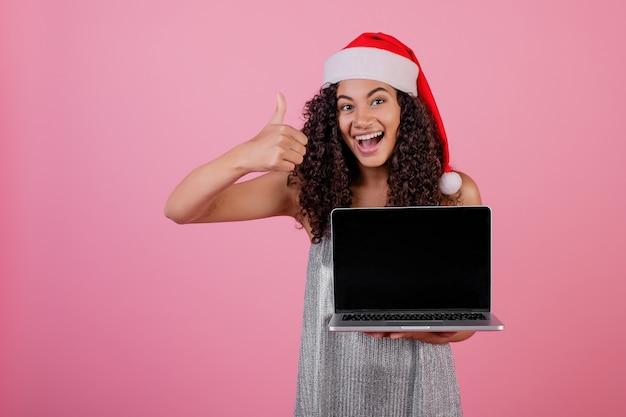 Linda mulher negra com tela copyspace no laptop usando chapéu de papai noel isolado sobre rosa