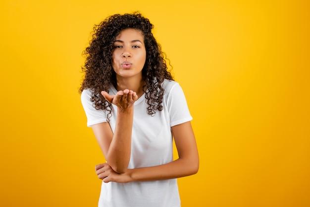 Linda mulher negra manda um beijo isolado sobre o amarelo