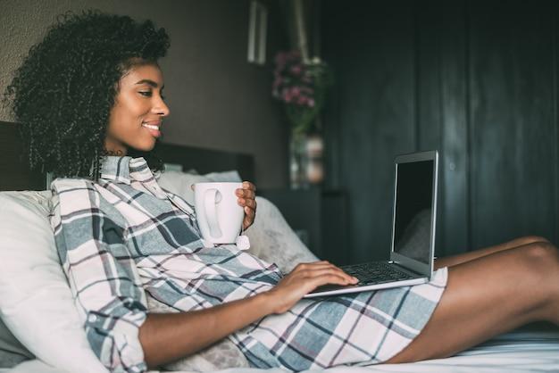 Linda mulher negra na cama com o laptop e a xícara de café