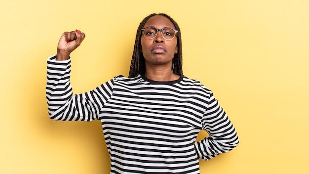 Linda mulher negra negra se sentindo séria, forte e rebelde, levantando o punho, protestando ou lutando pela revolução