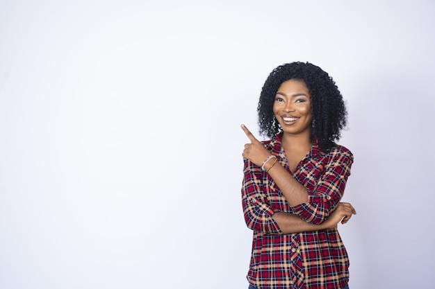 Linda mulher negra sorrindo e apontando para o espaço ao lado