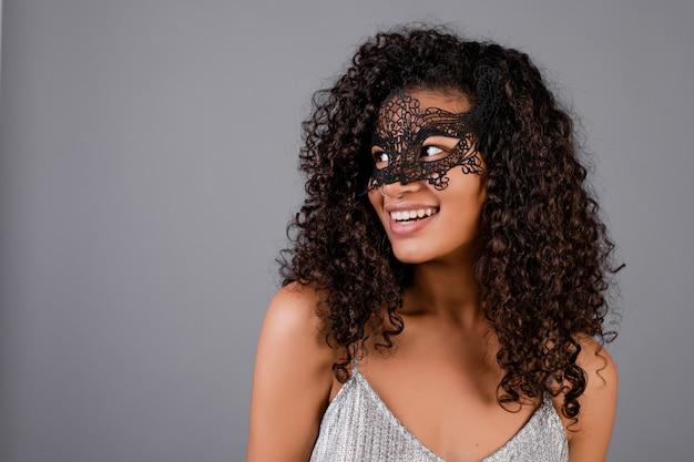 Linda mulher negra usando máscara de baile de máscaras elegante isolada sobre cinza
