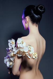 Linda mulher nua com um ramo de orquídea branca