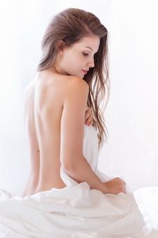 Linda mulher nua deitada na cama e cobrindo-se com lençol branco