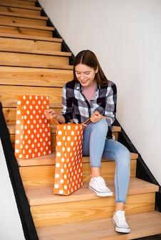 Linda mulher olhando para dentro de sacos, sentado na escada