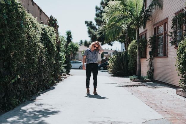 Linda mulher parada em um caminho vazio arrumando o cabelo