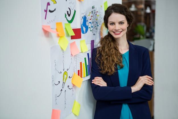 Linda mulher parada perto da parede com notas adesivas