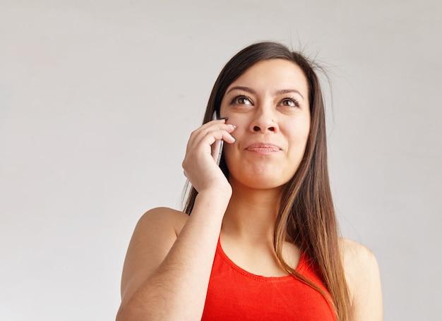 Linda mulher pensativa falando no smartphone e olhando para cima
