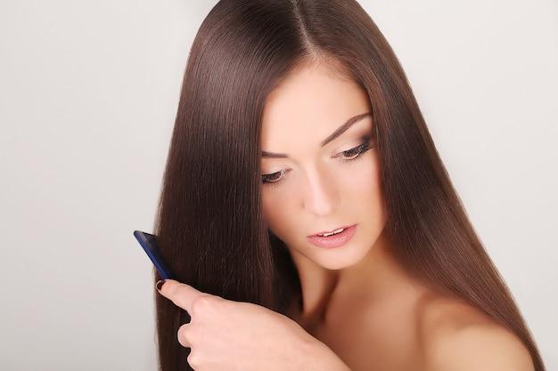 Linda mulher penteia seu cabelo longo saudável