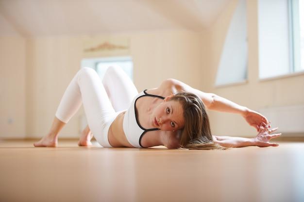 Linda mulher pratica ioga deitado asana torcido no estúdio de yoga