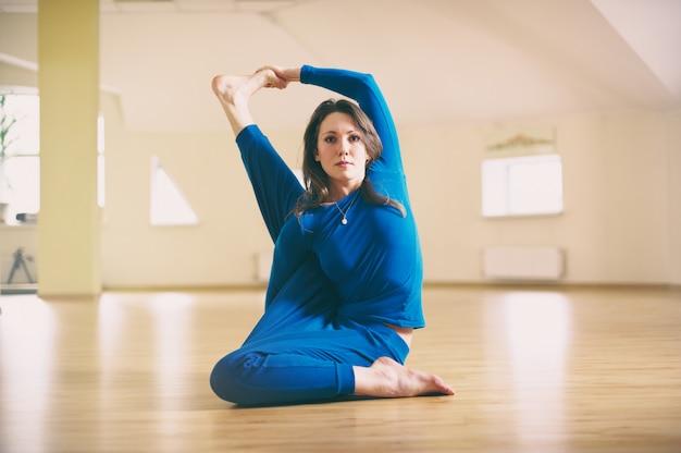 Linda mulher pratica ioga sentado asana torcida marichiasana no estúdio de yoga