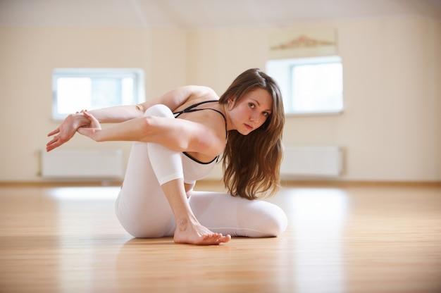 Linda mulher pratica ioga sentado asana torcido no estúdio de yoga