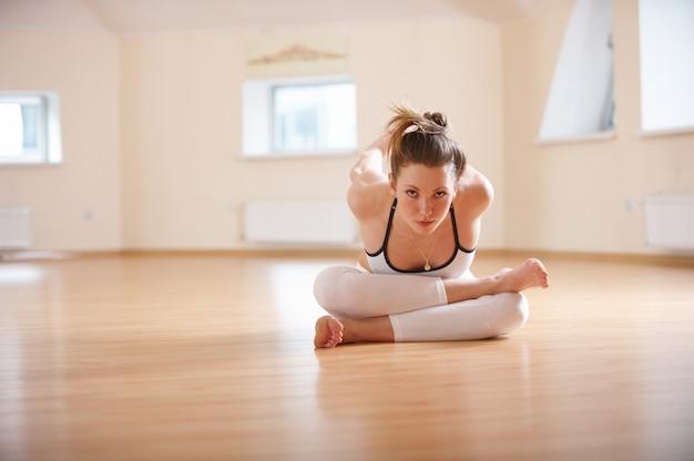 Linda mulher pratica yoga asana agnistambhasana. pose de log de fogo no estúdio de yoga