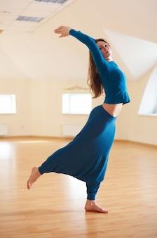 Linda mulher pratica yoga asana ardha chakrasana. pose de backbend em pé no estúdio de yoga