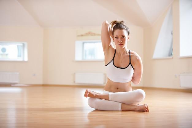 Linda mulher pratica yoga asana gomukhasana. pose de rosto de vaca no estúdio de yoga