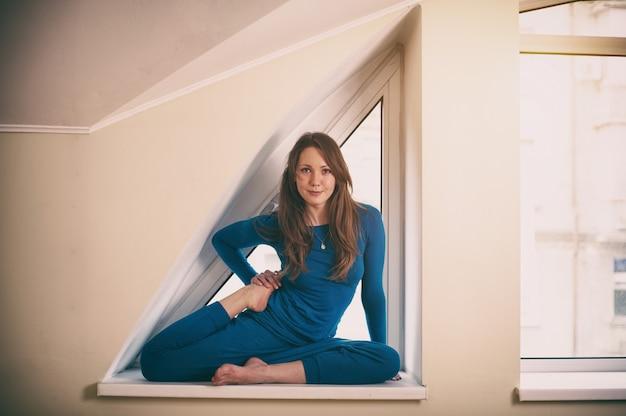Linda mulher pratica yoga asana vamadevasana. pose para o vamadeva no peitoril da janela