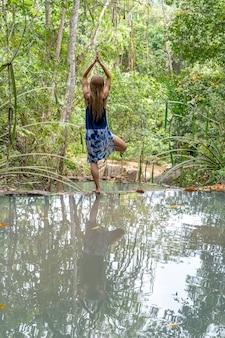 Linda mulher praticando ioga perto do lago da floresta. mulher jovem perto de água turquesa da cascata na floresta tropical profunda, ilha de koh phangan, tailândia
