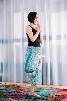 Linda mulher praticando yoga e meditação em casa