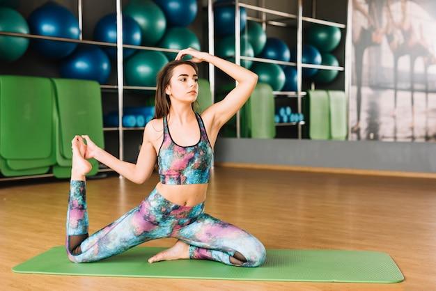 Linda mulher praticando yoga na esteira no ginásio