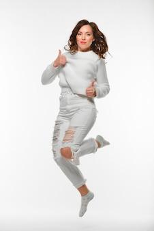 Linda mulher pulando enquanto olha para a câmera