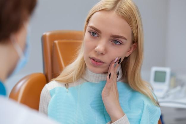 Linda mulher que sofre de dor de dente, visitar o dentista