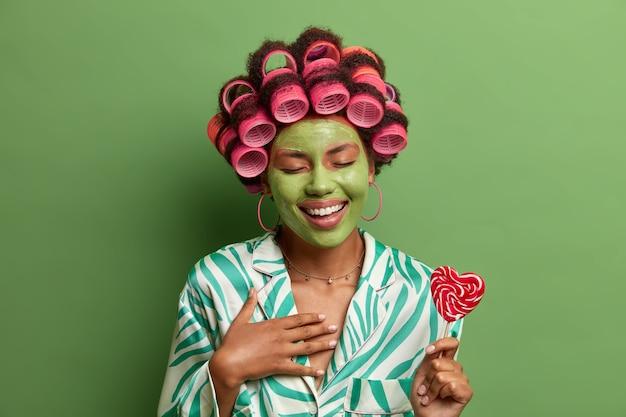 Linda mulher radiante com bobes e máscara facial verde, ri feliz, se diverte durante os procedimentos de beleza em casa, segura o pirulito no palito, se prepara para a festa tratamento de pele, bem-estar, spa