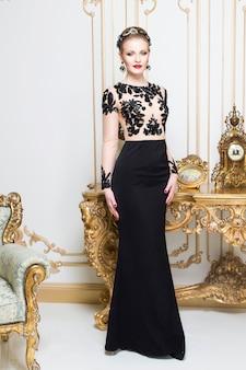 Linda mulher real loira em pé perto da mesa retrô com vestido de luxo. interior