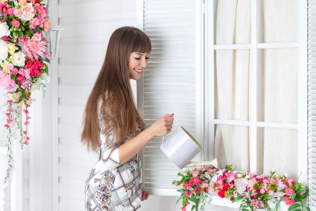 Linda mulher regando flores no peitoril da janela.