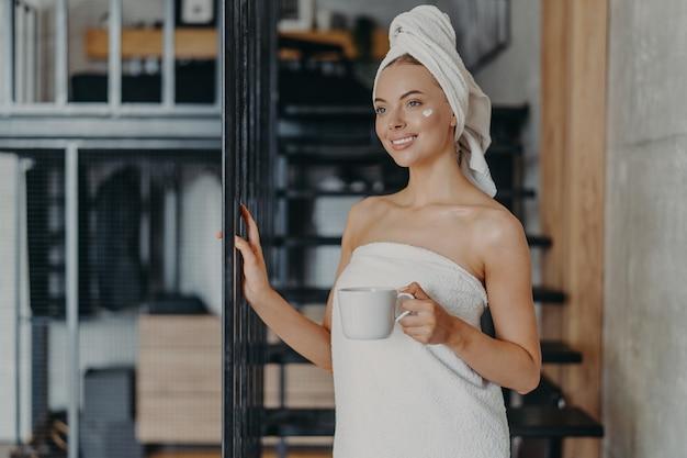 Linda mulher relaxada enrolada em uma toalha tomando chá