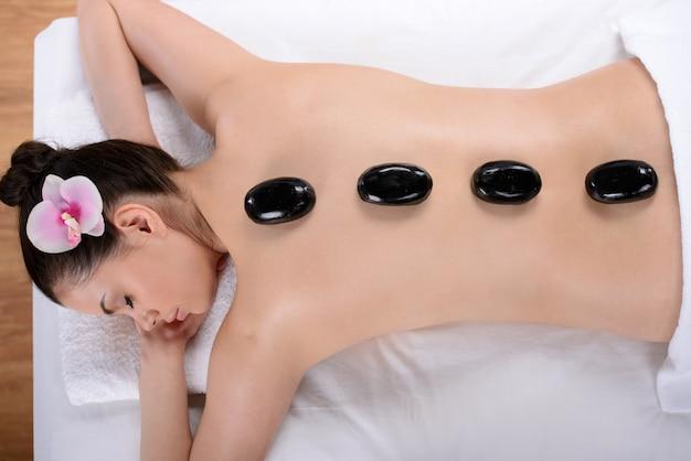 Linda mulher relaxante com pedras nas costas em um spa.