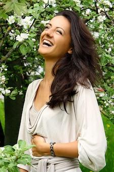 Linda mulher rindo pela árvore florescendo