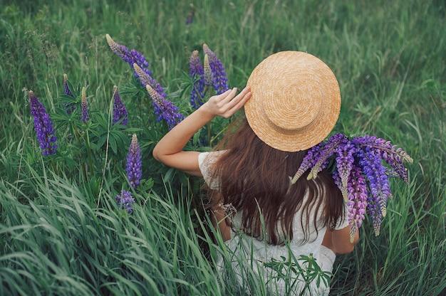 Linda mulher romântica com buquê de tremoços com alegria em vestido branco e chapéu senta-se no campo de flores roxas de tremoço.