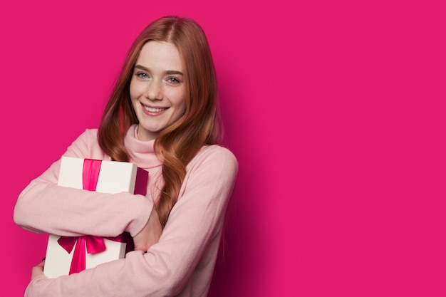 Linda mulher ruiva abraçando um presente e sorrindo para a câmera em uma parede rosa com espaço livre