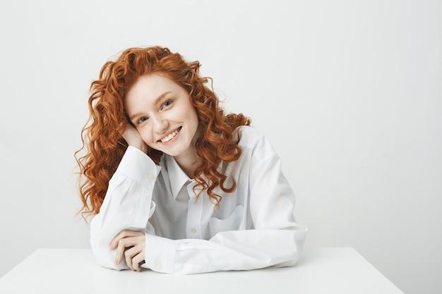 Linda mulher ruiva com cabelos cacheados, sorrindo, sentado à mesa.