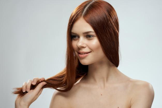 Linda mulher ruiva com cabelos lisos. cuidado capilar saudável e brilhante