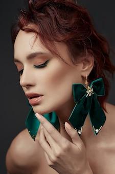Linda mulher ruiva com maquiagem e brincos verdes