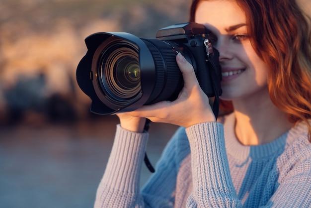 Linda mulher ruiva com uma câmera na natureza nas montanhas perto do rio